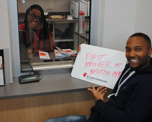 Banker smiling with first member at Benton Park branch.