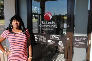 Woman smiling in front of St. Louis Community CU branch.