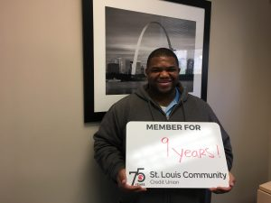 "St Louis Community member smiling while holding a sign, ""Member for 9 years!"""