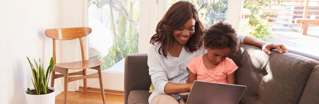 Mother and daughter sitting on couch looking at laptop