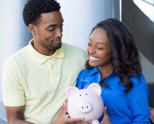 Man and woman smiling while holding a piggy bank.
