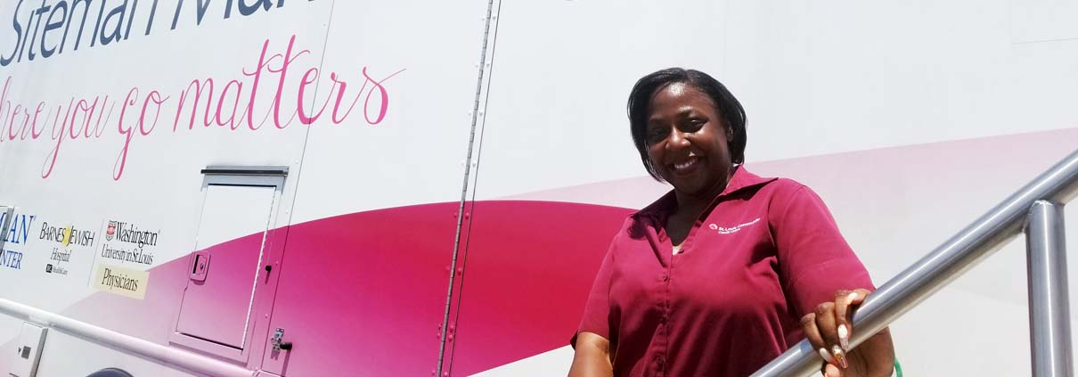 Woman smiling in front of Siteman Cancer Center bus