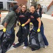 Women smiling while holding trash bags as they work for Mission Giveback