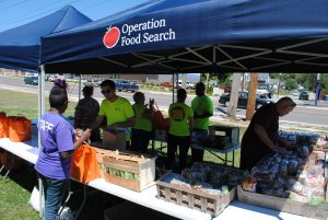 People distributing food at tent for Operation Food Search