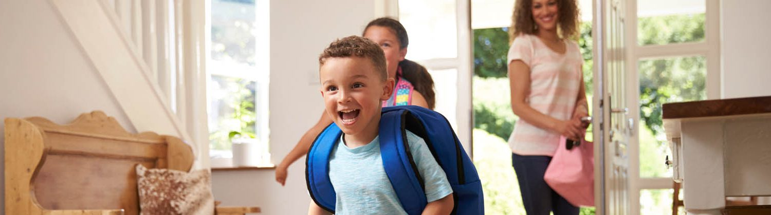 Children running into house with backpacks on smiling while mom stands in doorway smiling
