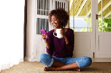 Woman holding coffee cup and smiling while looking at phone