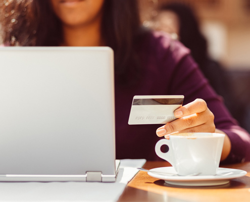 Woman sitting in coffee shop working on laptop and holding debit card.