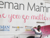 woman flexing in front of breast screening van